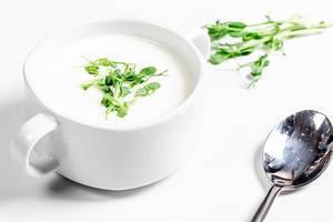 Weiße Pilzsuppe mit frischen Erbsprossen in einer weißen Terrine mit einem Löffel auf weißem Hintergrund