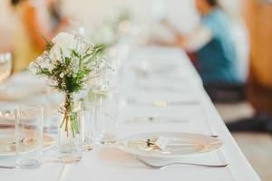 Weiße Rose in einer Glasvase in der Mitte eines Hochzeitstisches in Seitenansicht