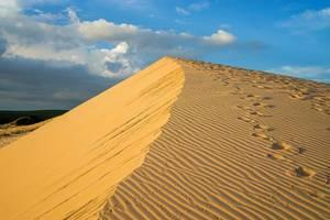 Weiße Sanddünen in Mui Ne, Vietnam mit Fußspuren und goldenen Reflektionen des Sonnenuntergangs
