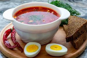 Weiße Schale mit Roter Beete Suppe, neben Chilischoten, halbierten Eiern, Brot und frischen Kräutern, auf einem runden Holzbrettchen
