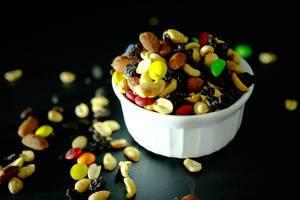 Weiße Schale, überfüllt mit Nussmix mit Rosinen und bunten Süßigkeiten vor dunklem Hintergrund