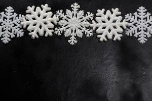 Weiße Schneeflocken Deko auf schwarzem Hintergrund mit Freiraum