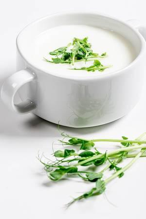 Weiße Suppe mit frischen Kräutern in einer Terrine