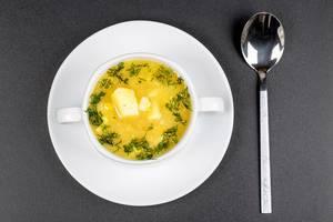 Weiße Suppentasse mit Erbsensuppe mit Kartoffeln und Dill auf einem weißen Teller mit Löffel von oben fotografiert