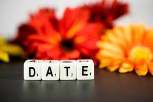 """Weiße Würfel mit Buchstaben zeigen das Wort Date """"Treffen"""", mit roten und orangen Blumen im Hintergrund"""