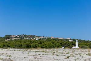 Weißer Leuchtturm unweit vom Strand
