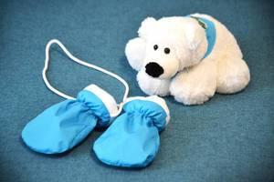 Weißer Plüsch-Eisbär mit blauem Dreieckstuch vor hellblau-weißen Baby-Fäustlingen mit Halskordel auf blauem Teppich