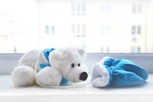 Weißer Teddybär mit blauem Dreieckstuch vor gleichfarbigen Baby-Fausthandschuhen auf weißem Fensterbrett