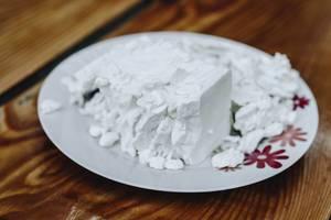Weißer Teller mit Fetakäse auf einem Holztisch