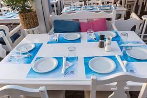 Weißer Tisch in Restaurant auf Paros ist gedeckt in den typisch griechischen Farben blau und weiß