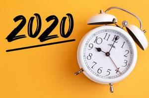 Weißer Wecker mit dem Text '2020' vor gelbem Hintergrund