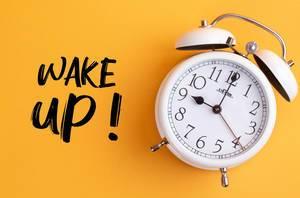 Weißer Wecker mit dem Text 'Wake up!' vor gelbem Hintergrund
