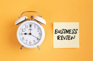 Weißer Wecker und ein Zettel mit 'Business Review' Text vor gelbem Hintergrund