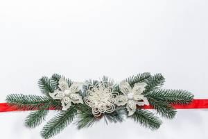Weißer weihnachtlicher Hintergrund mit Tannenzweig Dekoration und roter Schleife
