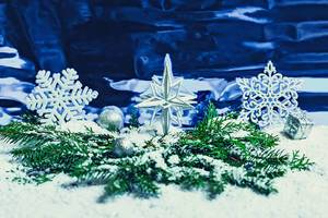 Weißer Weihnachts-Stern zwischen Tannenzweigen und Schneeflocken auf blauem Hintergrund