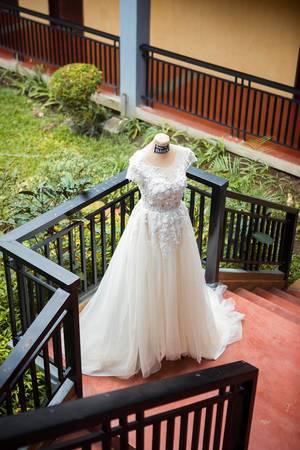 Weißes Brautkleid mit Spitze auf Puppe steht auf Treppenvorsprung im Hintergrund Garten