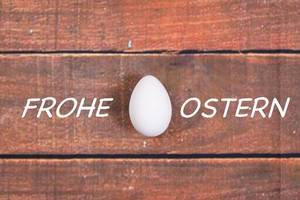Weißes Hühnerei eingebettet in Text FROHE OSTERN auf Hintergrund aus braunem Holz