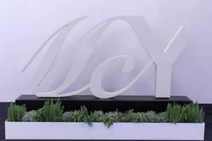 Weißes Logo von MCY (Monte Carlo Yachts) auf schwarzem Sockel mit Kakteen als Dekoration