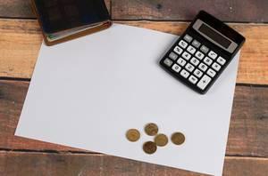 Weißes Papier auf einem Holztisch, mit Taschenrechner, Kleingeld und einem Portemonnaies