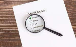 Weißes Papier mit ausgezeichnetem Kreditscore-Ergebnis unter einer Lupe auf einem Holztisch