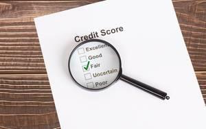 Weißes Papier mit fairem Kreditscore-Ergebnis unter einer Lupe auf einem Holztisch