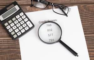 Weißes Papier mit Kreditscore-Ergebnissen mit Lupe, Lesebrille und Taschenrechner auf einem Holztisch