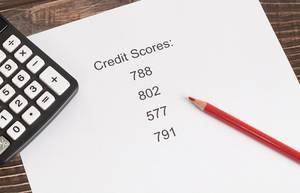 Weißes Papier mit Kreditscore-Ergebnissen mit rotem Holzstift und Taschenrechner auf einem Holztisch