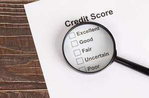Weißes Papier mit Kreditscore-Ergebnissen unter einer Lupe auf einem Holztisch