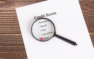 Weißes Papier mit schlechtem Kreditscore-Ergebnis unter einer Lupe auf einem Holztisch