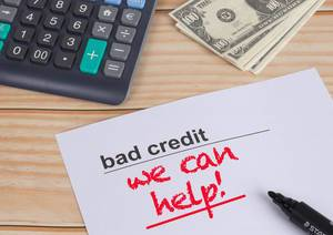 Weißes Papier mit schwarzem Text Bad Credit und rotem Text We Can Help mit schwarzem Filzstift, Taschenrechner und Dollar Geldscheinen auf einem Holztisch