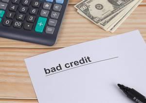 Weißes Papier mit Text Bad Credit mit schwarzem Filzstift, Taschenrechner und Dollar Geldscheinen auf einem Holztisch