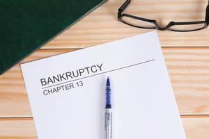 Weißes Papier mit Wort Bankruptcy mit Kugelschreiber und Lesebrille auf einem Holztisch