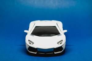 weißes Spielzeugauto isoliert auf blauem Hintergrund