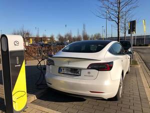 Weißes Tesla Fahrzeug wird bei einer Innogy Ladestation für Elektroautos geladen