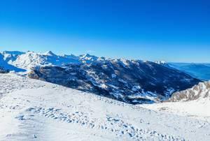 Weitblick von Gipfel über die umliegenden, verschneiten Berge bei Vars mit blauem Himmel
