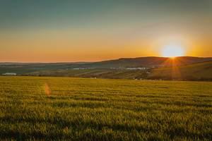 Weite Felder vor einem schönen Sonnenuntergang am Horizont, mit warmen Farben im Süden von Mähren, Tschechien