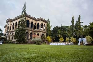 Weitwinkelaufnahme von verlassener Villa mir Aufbau für Hochzeit im dazugehörigen Garten