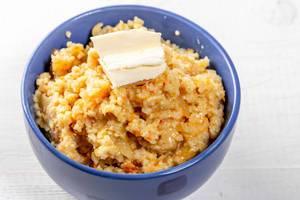 Weizen-Porridge mit einem Stück Butter in einer blauen Schale