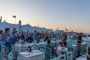Well visited restaurant terrace at the harbour at sunset on Paros, Greece