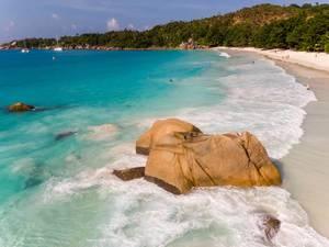 Wellen des Indischen Ozeans brechen am Granitstein neben dem Strand Anse Lazio auf Praslin, Seychellen