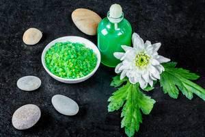 Wellnesszubehör wie Schale mit grünem Badesalz, grünes Gel und Steine mit Blume auf schwarz