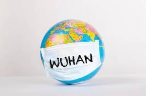 Weltkugel mit den Wort Wuhan auf einer Gesichtsmaske auf weißem Hintergrund