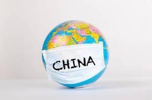 Weltkugel mit Gesichtsmaske mit den Worten China vor weißem Hintergrund