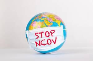 Weltkugel mit Gesichtsmaske und Text Stop NCOV Coronavirus auf weißem Hintergrund