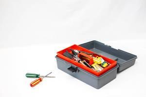 Werkzeugkasten und zwei Schraubendreher vor weißem Hintergrund