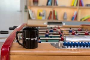 WeWork-Tasse auf einem Tischfußball im Gemeinschaftsbereich des Coworking Space in Köln