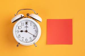White alarm clock on yellow background with empty red sticky note