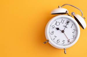 White alarm clock on yellow background with empty space