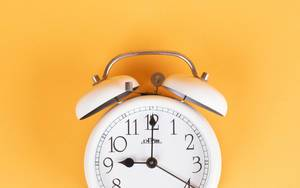 White alarm clock on yellow background