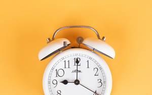 White alarm clock on yellow background